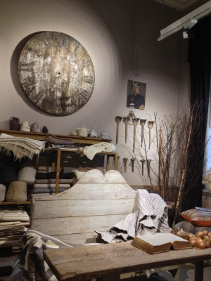 The natural room with a giant clock and some wool combs hanging on the wall.