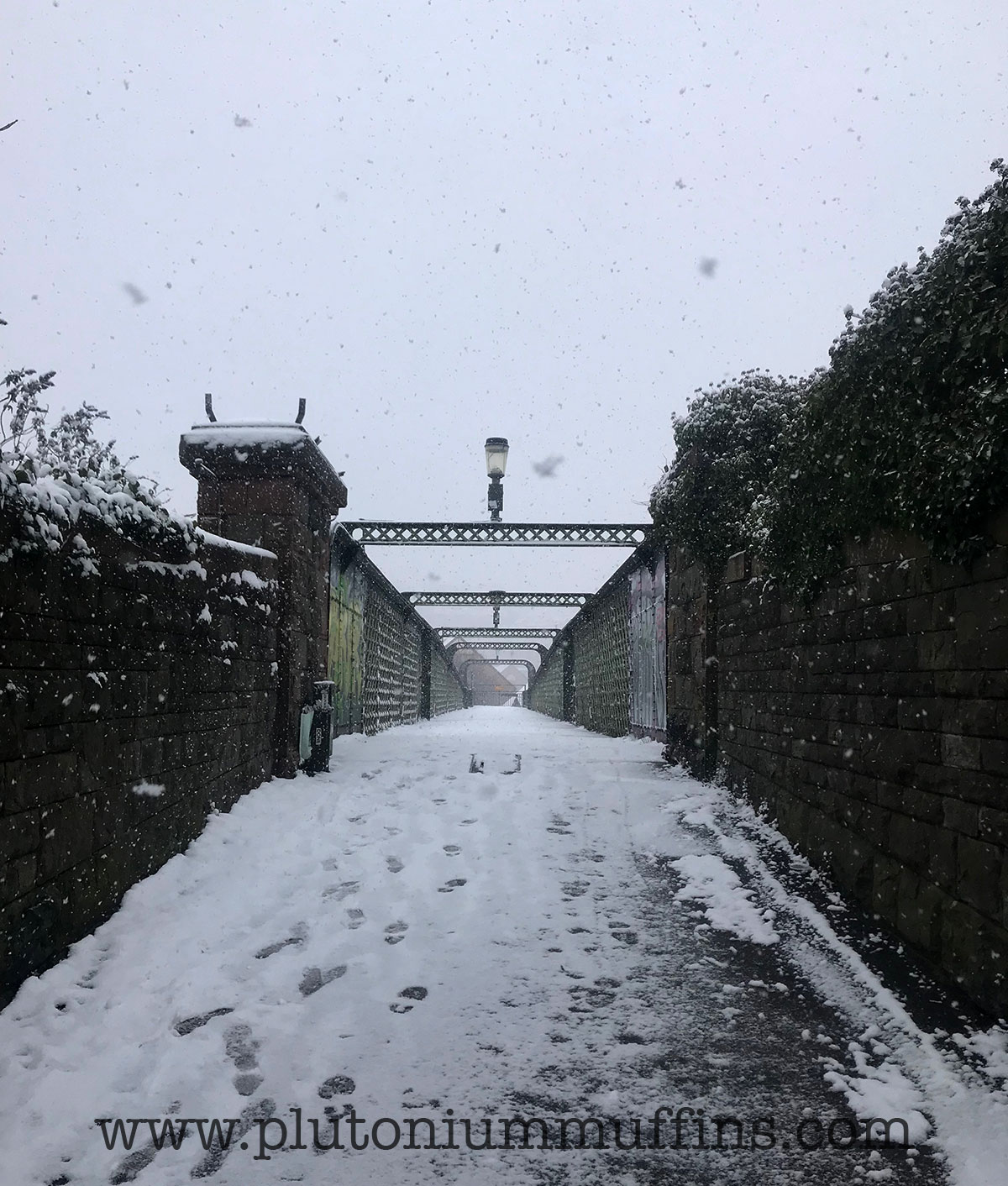 A bridge with a Narnia style lamp on the top, heavy snow falling.