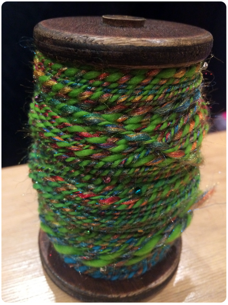 A bobbin full of the first yarn.