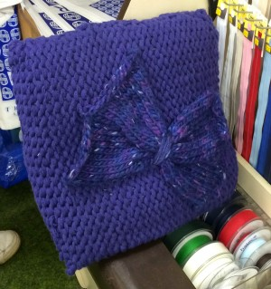A beautiful knitted cushion in the shop.