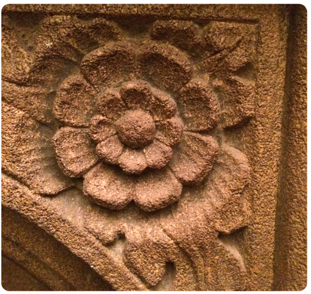 An English rose carved into a fireplace inside.