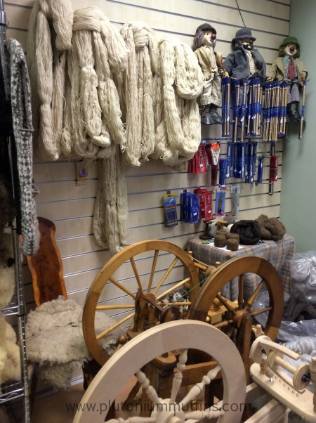 Skeins of yarn and spinning wheels, with some notions on the right.