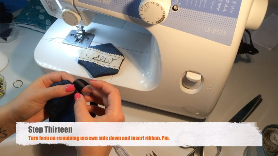 Step Thirteen: Turn hem on remaining unsewn side down and insert ribbon. Pin.