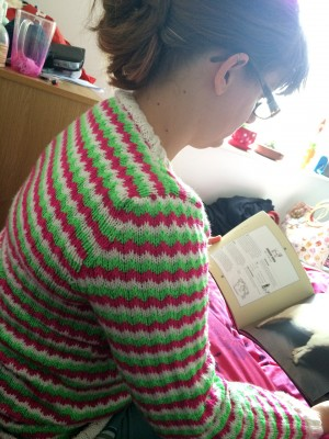 "Sneaky ""Corrie wearing Zigzag Jumper reading about sheep"" photo. Thanks John!"